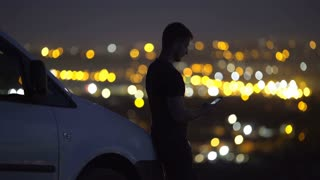 The success man stand near the car on the background of night city light. Wide angle. Real time capture