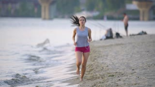 The woman run on the beach and listen music by river and bridge background