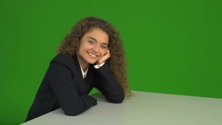 The young curly woman sit and smile on the green background. Real time capture