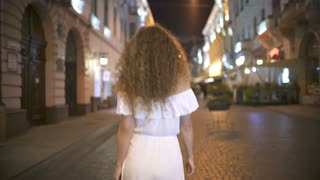 The young woman walk on the evening street. Real time. Wide angle