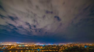 Clouds stream on the background of the city. night to day transition. time lapse