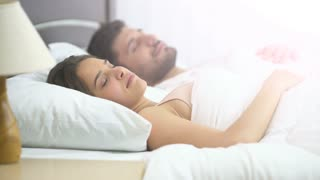 The attractive woman sleeping near the man on the bed