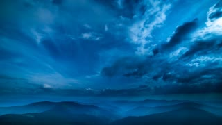 The beautiful mountain landscape on a cloud flow background. evening night time