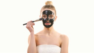 The beautiful woman applying a black face mask on the white background