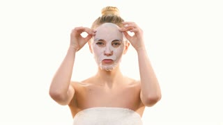 The beautiful woman removing a clean face mask on the white background