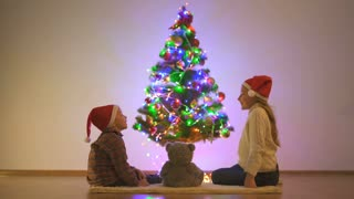 The boy and a girl sit on the floor near the christmas tree