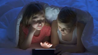 The boy and a girl using a tablet under the bed. evening night time