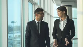 The business man and a woman talking near windows in the office. slow motion