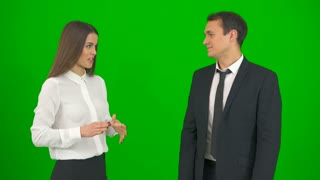 The business man and woman laugh on the green background