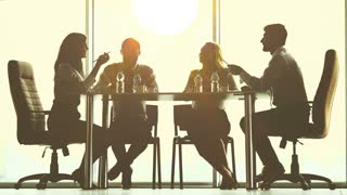 The business people sit at the table in a sunny background