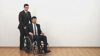 The businessman walking with a disabled on a wheelchair on the white background