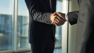 The businessmen handshake in the office. slow motion