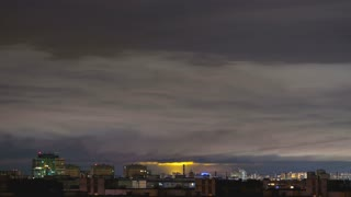 The clouds stream above the night city. time lapse