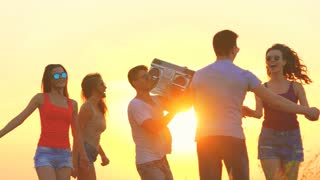 The company of people with a boom box dancing on a dawn background. slow motion