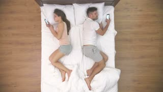 The couple lay with phones in the bed. view from above