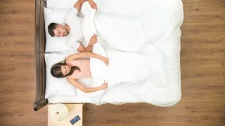 The couple relax all day in the bed. view from above. time lapse
