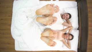 The couple shake feet in the bed. view from above