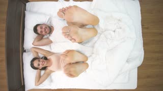 The couple shake legs in the bed. view from above
