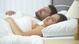 The couple sleeping in the bed