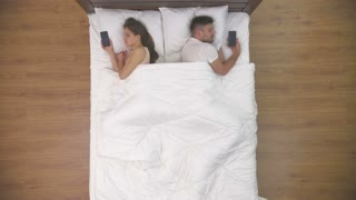 The couple sleeping with phones in the bed. view from above