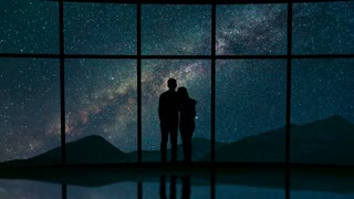 The couple stand near a window against the meteor shower in the sky. time lapse