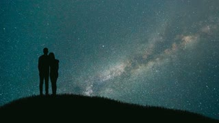 The couple stand on the montain on the starry background. time lapse, night time