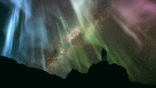 The couple standing on the rock against a starry sky with a northern light