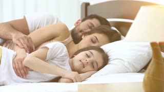 The cute family sleeping on the bed