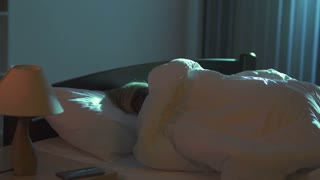 The cute woman lay on the bed and phone. Evening night time