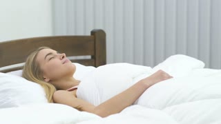 The cute woman lay on the bed. Real time capture