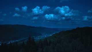 The dark picturesque mountains cloudy landscape with city in the valley at night