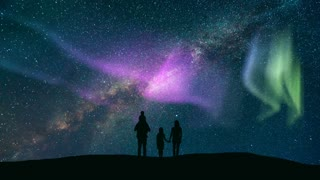 The family standing against a starry sky with a northern light. time lapse