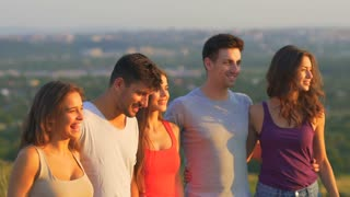 The five happy people stand on the background of the city. slow motion