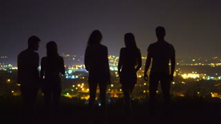 The five people stand on the background of the city lights. evening night time