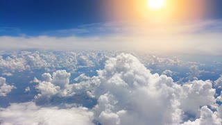 The flighting above the beautiful clouds on the bright sun background