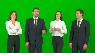 The four business people work with a virtual screen on the green background