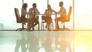The four people sit at the table and talk on the background of the bright sun