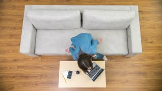 The freelancer woman work with a laptop on the sofa. Time lapse