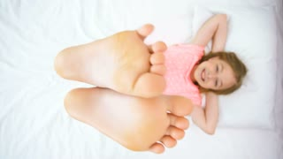 The girl doing exercise with legs on the bed. view from above