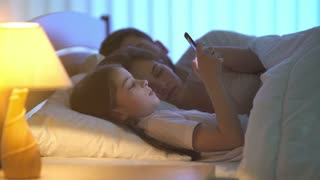 The girl hold a phone on the bed near parents