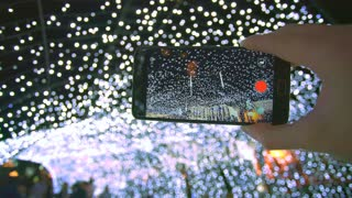 The hand with a smartphone shot the bright lights. Real time capture