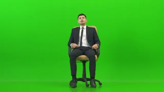 The happy businessman turning on the office chair on the green background