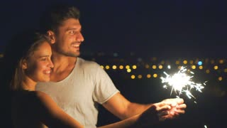 The happy couple hold bengal lights on a background of a night city. slow motion