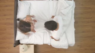 The happy couple jump in the bed. view from above