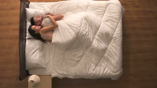 The happy couple sleeping in the bed. view from above