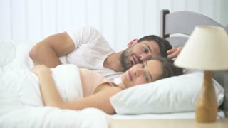 The happy man and woman kissing in the bed