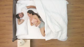 The happy man and woman talk in the bed. view from above