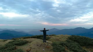 The happy man on the mountain enjoying the scenic landscape