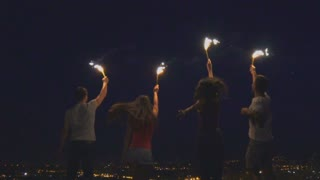 The happy people hold firework sticks. slow motion, evening night time