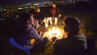 The happy people rest near the campfire. evening night time
